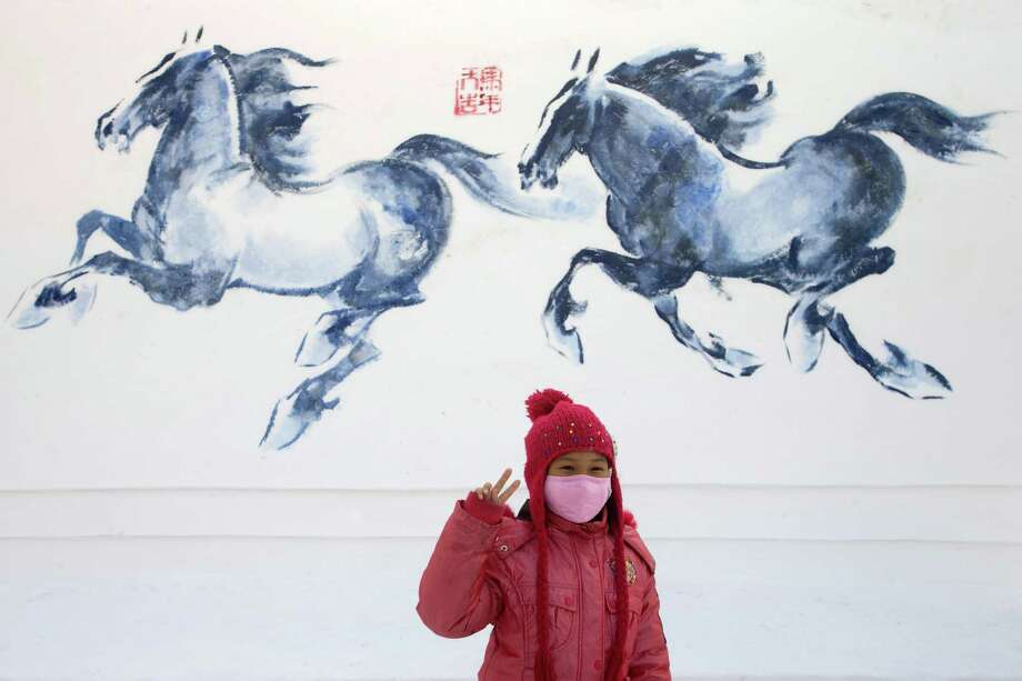 Here a girl poses for a photograph beside a snow sculpture depicting horses. Photo: Hong Wu, Getty Images / 2013 Hong Wu