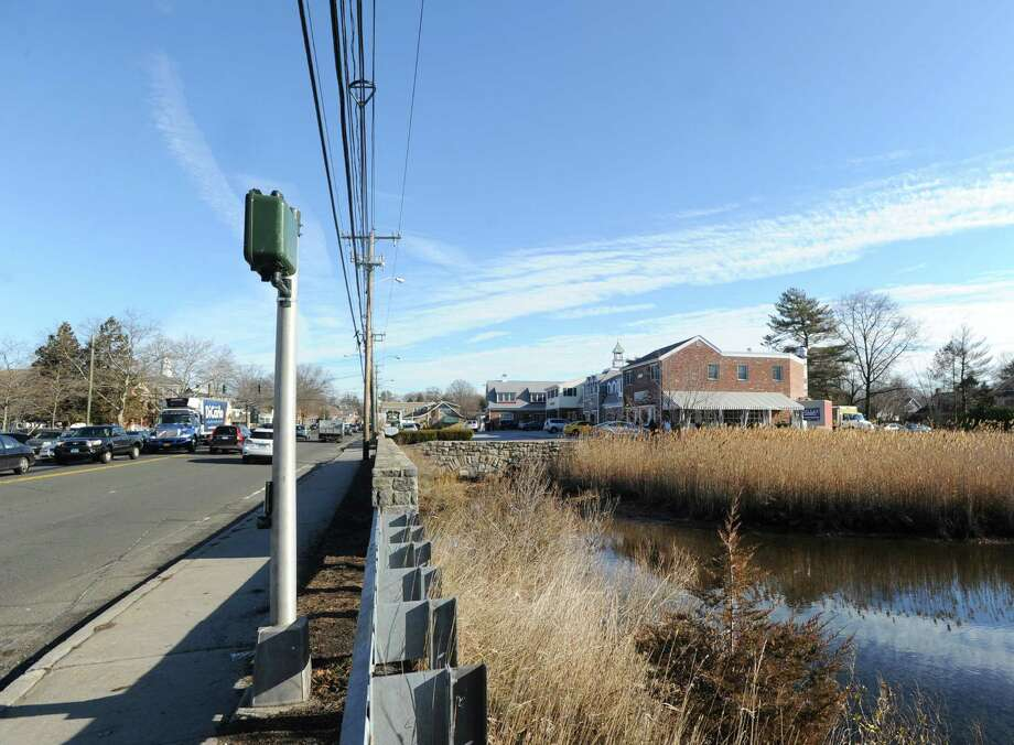 The Mill Pond, right, and Mill Pond Shopping Center, background right, are visible as traffic passes on East Putnam Avenue in downtown Cos Cob, Tuesday, Dec. 24, 2013. Photo: Bob Luckey / Greenwich Time