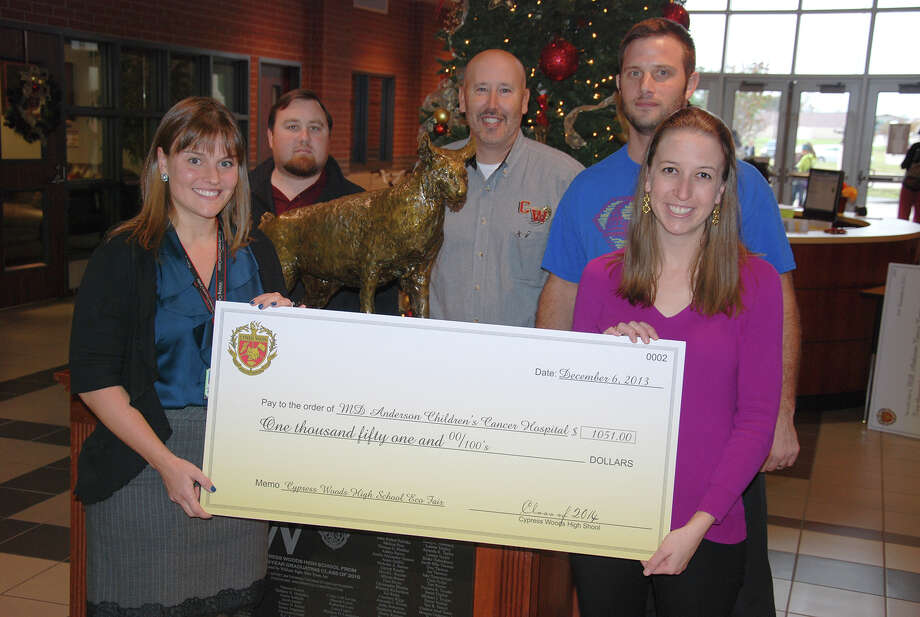 From left, Tracey Honea of MD Anderson and Cy-Woods teachers Wes Schroller, Thomas White, Michael Vance and Emily Tate show a check donated through school fundraisers. Photo: Provided By Cy-Fair Independent School District