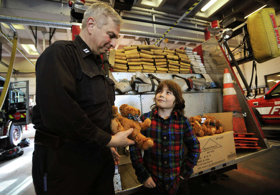 Bridgeport Fire department Captain Peter Oliva accepts a donation of 24 teddy bears from Vladimir Romano, 10, of Redding, at Bridgeport Fire department headquarters in Bridgeport, Conn. on Tuesday, December 24, 2013. Romano, who raises money to purchase the bears by running a summer lemonade stand, has donated 400 bears to area fire departments over the last 3 years. Photo: Brian A. Pounds / Connecticut Post