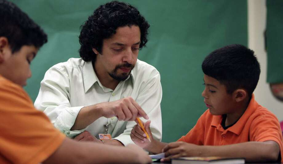Fourth-grade teacher Michael Peña, shown with Mission Academy students in 2012 when he was working on a master's degree in bilingual studies, might one day also have his bilingual work stored at UTSA's archives. Photo: Express-News File Photo / ©SAN ANTONIO EXPRESS-NEWS