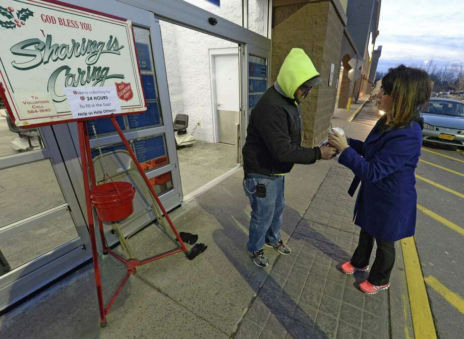 Eric Dworak receives a welcome cup of hot coffee from Lisa Cammerene Tuesday morning, Dec. 24, 2013, in front of the Walmart in Clifton Park, N.Y.  Dworak and his associate William Harwood are doing a marathon bell ringing to pump up the donations to the Salvation Army Kettle Fund this year. (Skip Dickstein / Times Union) Photo: Skip Dickstein / 00025150A