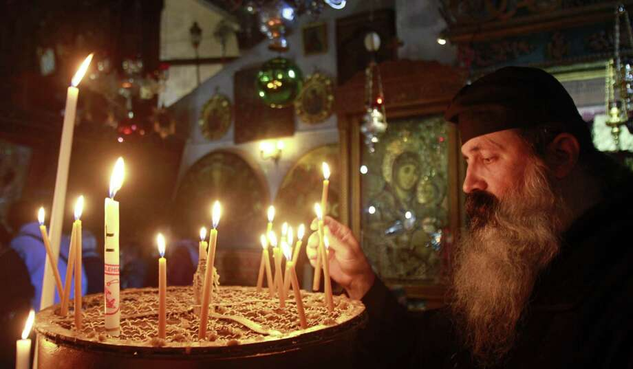 A Greek Orthodox priest lights a candle in the Church of the Nativity in Bethlehem as he prepares to celebrate the birth of a deity who embodied radical values. Photo: Getty Images / AFP