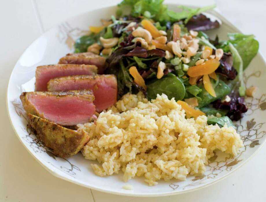 This Nov. 18, 2013 photo shows coconut cashew salad with apricots and seared curry rubbed tuna with mango tahini rice in Concord, N.H. It's a mash-up that draws on the flavors of the Caribbean, Southeast Asia and Europe. (AP Photo/Matthew Mead) ORG XMIT: MER2013122011374671 Photo: Matthew Mead / FR170582 AP