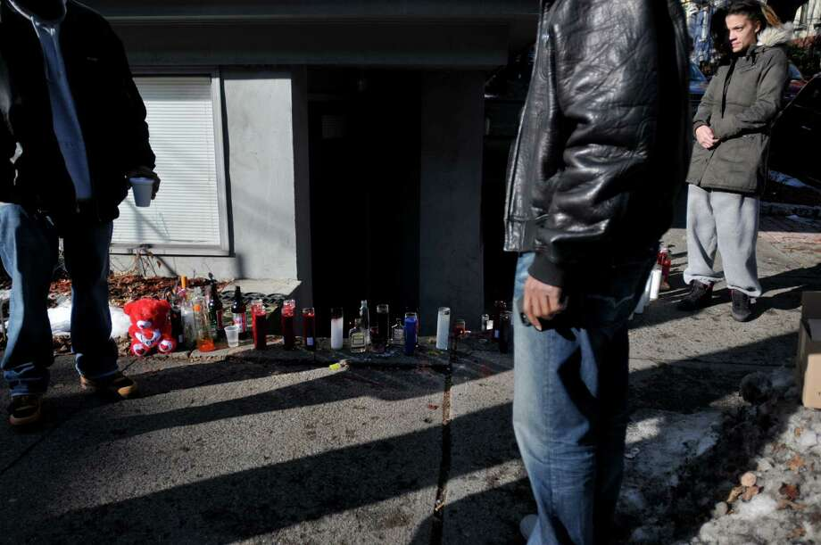 People gather near a memorial set up for Sylvester Scott on Grand St. on Tuesday, Dec. 24, 2013, near the site where Scott was fatally shot Monday morning in Albany, NY.   (Paul Buckowski / Times Union) Photo: PAUL BUCKOWSKI / 00025159A