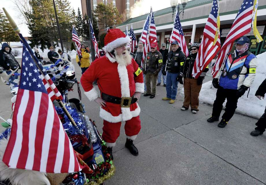 Santa Claus(Dean Courter of Troy) gets everyone in the Christmas spirit Dec. 24, during the prelude to the 10th Anniversary Christmas Eve Road March in Glens Falls.  The Christmas Eve Road March was conducted in 2004 when soldiers of the New York Army National Guard's Company C, 2nd Battalion 108th Infantry, which was then based at the now-closed Glens Falls Armory, were away from home in Iraq over Christmas. Other soldiers assigned to the armory, from the 466th Area Medical Company, got together to conduct a road march, the military term for a walking movement, in their honor. The march is sponsored, in part, by the Capital District of New York Chapter of the Association of the U.S. Army.  (Skip Dickstein / Times Union) Photo: Skip Dickstein / 00025155A