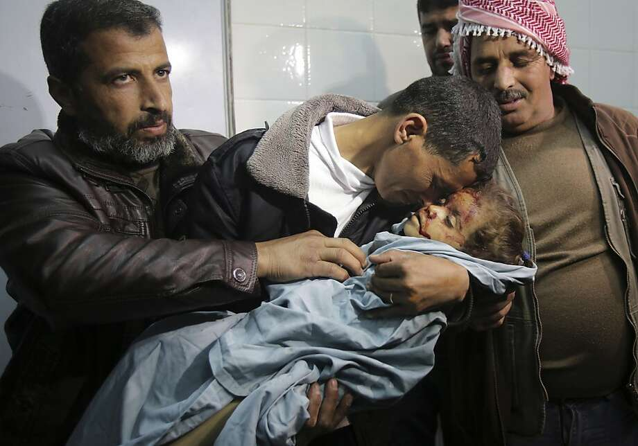 A Palestinian man cradles the lifeless body of his niece, 3-year-old Hala Abu Sebakha, who medics said was killed by shrapnel during an Israeli air strike on the Al Maghazi camp, at the morgue of Al-Aqsa hospital in Deir Al Balah, central Gaza Strip, Tuesday, Dec. 24, 2013. Israeli air and ground forces launched a series of attacks Tuesday on targets across the Gaza Strip, killing the young girl and wounding 10 in response to the deadly shooting of an Israeli civilian by a Palestinian sniper. (AP Photo/Adel Hana) Photo: Adel Hana, Associated Press