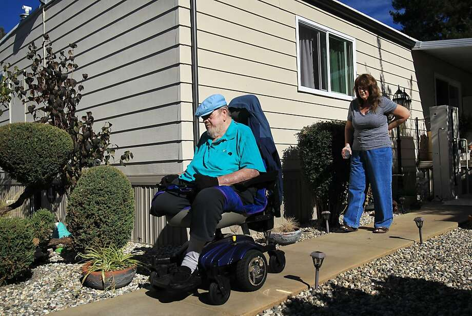 Donald Keen steers his wheelchair down the walkway beside his Napa home as his sister, Donna Greer, helps him navigate. A top-notch portable ramp gives Keen access to the mobility he had long been missing. Photo: Leah Millis, The Chronicle