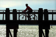 John Bianchi, of North Haven, rides out onto the pier at Gulf Beach during his 40 mile bike ride in Milford, Conn. on Tuesday December 24, 2013.