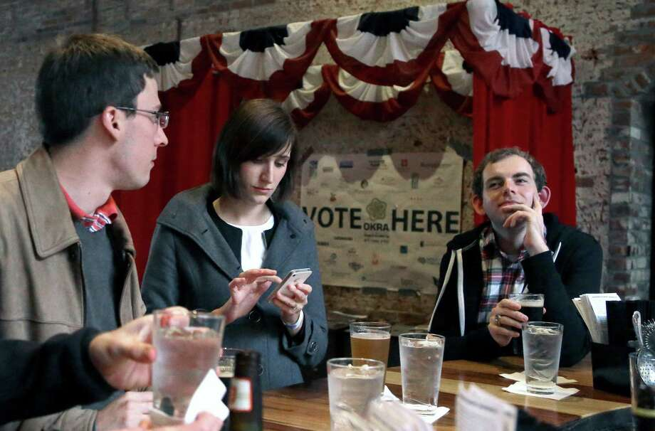 In this Dec. 13, 2013 photo, Jesse Mello, left, Erin Holt, center, and Matt Pankey enjoy drinks at The Original OKRA Charity Saloon in Houston. The gives 100 percent of its profits to charity and is set to donate more than $300,000 after its first year.(AP Photo/Pat Sullivan) Photo: Pat Sullivan, STF / AP