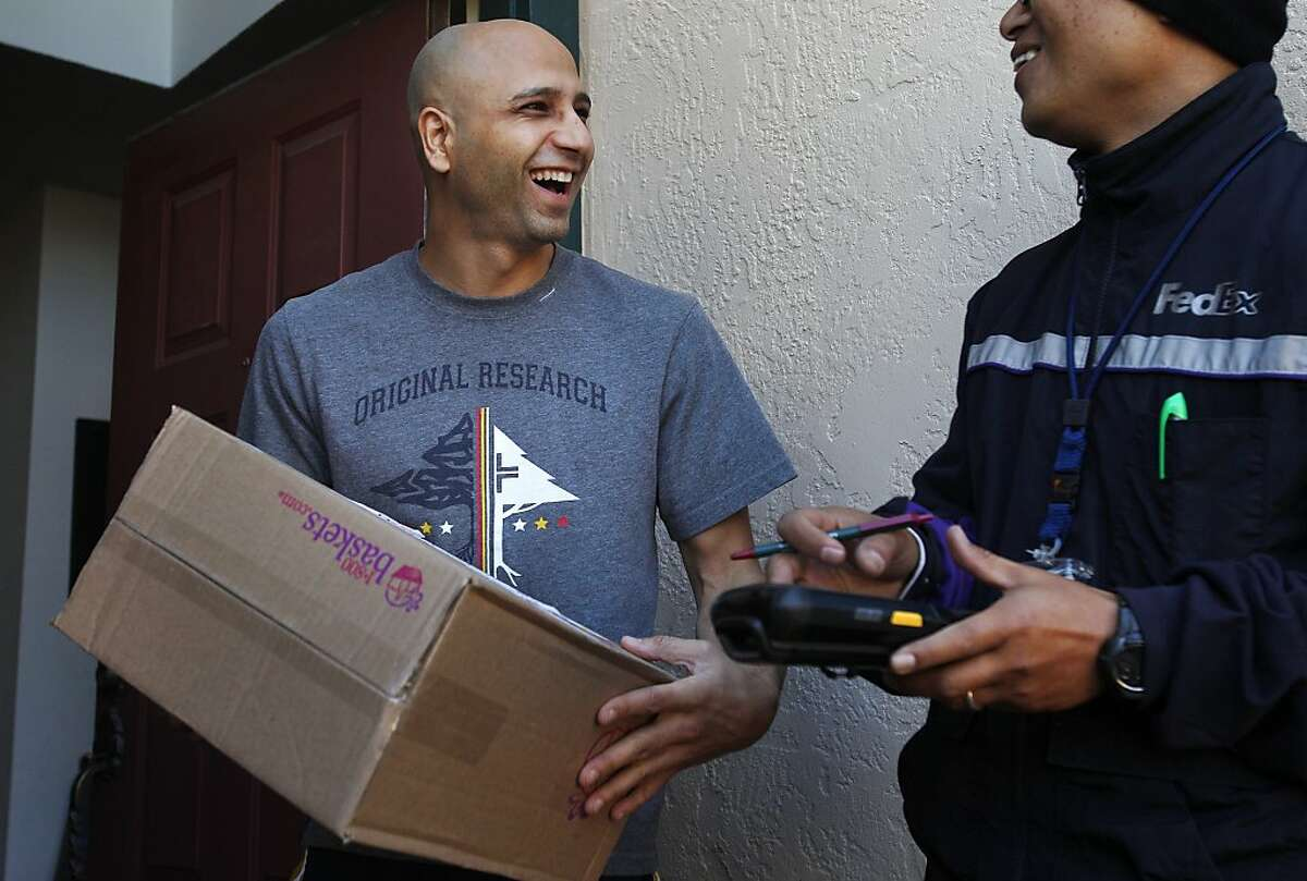 Kais Shirgul, left, reacts after discovering he received a package from his manager that Ben Tilos, right, delivered to him during Tilos' route December 24, 2013 in Alameda, Calif. FedEx says this year has been especially busy for the company, especially this close to Christmas. Tilos thinks a lot of the surge in packages has to do with the increase in internet shopping.