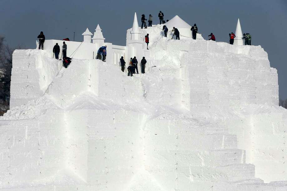 Someone has to make these sculptures. Here workers carve a castle.  Photo: Hong Wu, Getty Images / 2013 Hong Wu