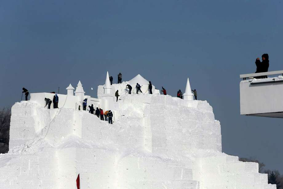 It's cold work, carving a castle. . Photo: Hong Wu, Getty Images / 2013 Hong Wu