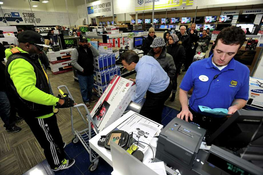 FILE - In this Nov. 29, 2013, file photo, Best Buy employee Christopher Gervais, right, rings up a 32-inch LED TV in Dunwoody, Ga.  Sales at U.S. stores dropped 3.1 percent to $42.7 billion for the week that ended on Sunday, Dec. 22, 2013, compared with the same week last year, according to ShopperTrak, which tracks data at 40,000 locations. (AP Photo/David Tulis, File) ORG XMIT: NY117 Photo: David Tulis / FR170493 AP