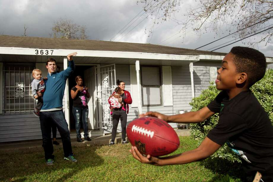 Texans linebacker Brian Cushing plays catch with Darius Montgomery last week after Cushing and his wife, Megan, surprised Darius and his mother, Evelyn Smith, back left, with a houseful of Christmas gifts. Photo: Brett Coomer, Staff / © 2013 Houston Chronicle