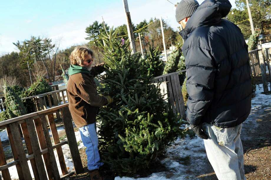 Assistant manager Brian Whalen, left, sells a Christmas tree to a customer on Tuesday, Dec. 214, 2013, at Hewitt's in Guilderland, N.Y. (Cindy Schultz / Times Union) Photo: Cindy Schultz / 00025143A