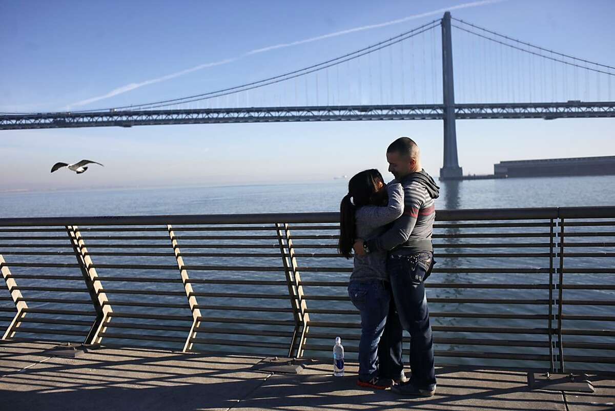 """Nancy Dominguez, left, and Julian Haro hold each other as they enjoy the view of the Bay Bridge and the weather, Tuesday December 14, 2013 along the Embarcadero in San Francisco, Calif. They met on an online dating service and she is visiting from for the holidays from Santa Monica. """" I brought the the warm weather with me, you can't beat the weather in Santa Monica,"""" says Dominguez."""
