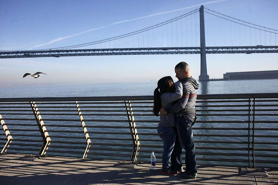 "Nancy Dominguez, left, and Julian Haro hold each other as they enjoy the view of the Bay Bridge and the weather, Tuesday December 14, 2013 along the Embarcadero in San Francisco, Calif. They met on an online dating service and she is visiting from for the holidays from Santa Monica. "" I brought the the warm weather with me, you can't beat the weather in Santa Monica,"" says Dominguez. Photo: Lacy Atkins, The Chronicle"