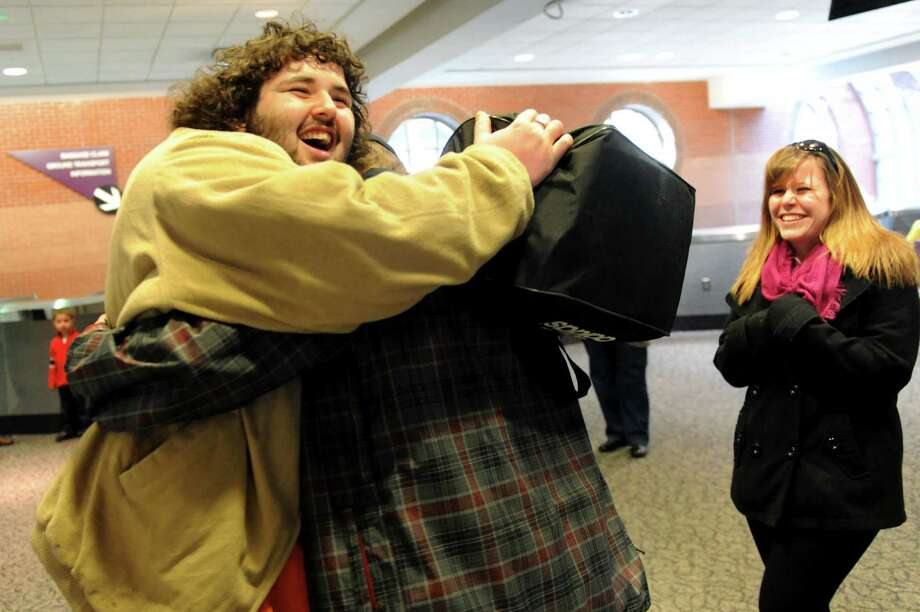 Nate McMillan of North Adams, Mass, left, embraces his best friend Charles Lee Martin Jr., who's home for the holidays from Sylvan Lake, Mich., on Tuesday, Dec. 24, 2013, at Albany International Airport in Colonie, N.Y. At right is Martin's sister Kori Forrest of North Adams, Mass. (Cindy Schultz / Times Union) Photo: Cindy Schultz / 00025153A