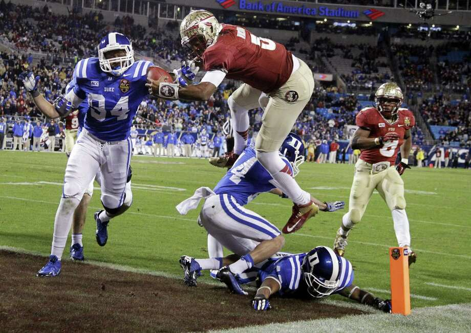 Florida State freshman quarterback Jameis Winston (center), leaping over Duke's Bryon Fields (14) for a touchdown in the ACC championship game, added to his list of accolades Tuesday. Photo: Bob Leverone / Associated Press / FR170480 AP