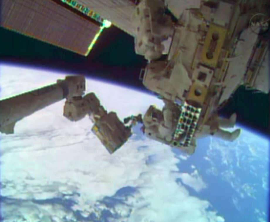 In this image taken from video provided by NASA, astronauts Rick Mastracchio, top, and Michael Hopkins work to repair an external cooling line on the International Space Station on Monday, Dec. 24, 2013, 260 miles above Earth. The external cooling line — one of two — shut down Dec. 11. The six-man crew had to turn off all nonessential equipment, including experiments. (AP Photo/NASA) Photo: HOPD / NASA