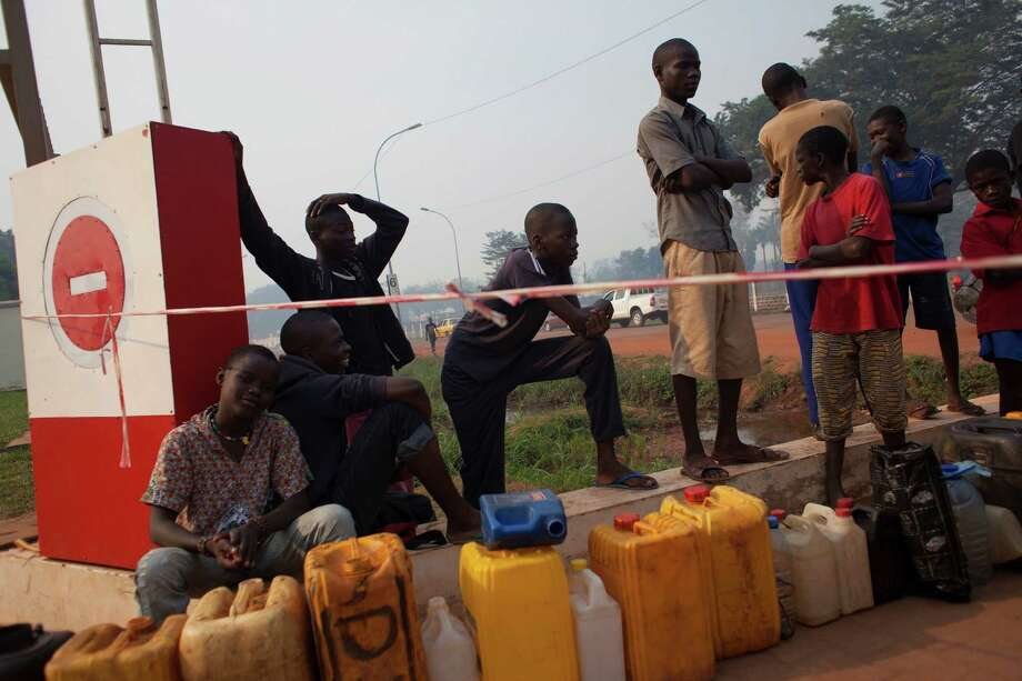 People waiting to purchase fuel hold their places in line with jerrycans, at a gas station that was closed, awaiting the arrival of military police, in Bangui, Central African Republic, Tuesday, Dec. 24, 2013. With few gas stations open and reliable fuel hard to find, people lined up as early as 4 a.m. at this station, which wasn't slated to open until police protection arrived around 9 or 10 a.m. (AP Photo/Rebecca Blackwell) Photo: Rebecca Blackwell, STF / AP