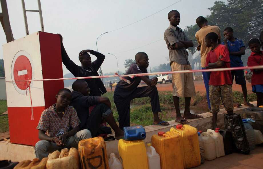 People wait to purchase fuel at a gas station that hadn't opened yet in Bangui, Central African Republic. The station wouldn't open till police arrived. Photo: Rebecca Blackwell / Associated Press / AP