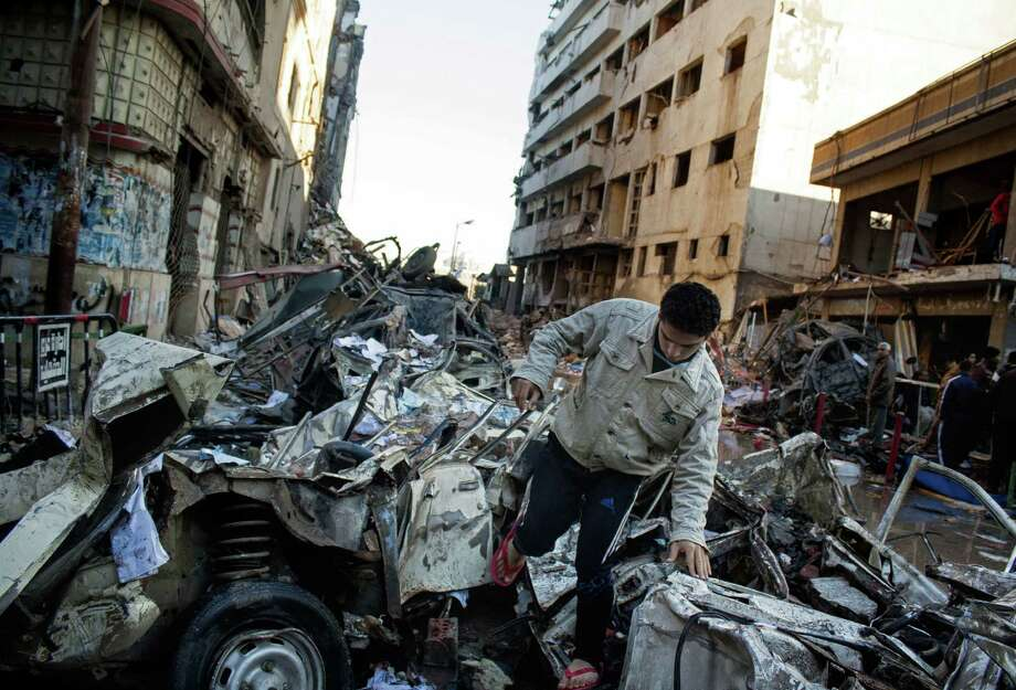An Egyptian man makes his way through rubble after  an explosion at a police headquarters building in the Nile Delta city of Mansoura, north of Cairo. It was the second attack on the police building since July. Photo: Ahmed Ashraf / Associated Press / AP