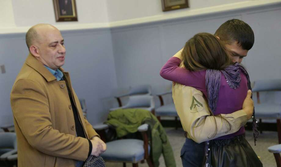 Lance Cpl. Christopher Mohedano-Hernandez (right) is hugged by his sister Kate Mohedano, 12, while his stepfather Luis Mohedano looks on after an adoption ceremony Tuesday in Mineola, N.Y. Photo: Seth Wenig / Associated Press / AP