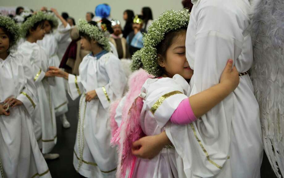 Tammy Vo, 5, embraces her angel leader Diane Nguyen, 16, just before the Mass procession during The Christmas Eve Mass for the Vietnamese Community, Tuesday, Dec. 24, 2013, in Houston. Photo: Marie D. De Jesus, Houston Chronicle / © 2013 Houston Chronicle