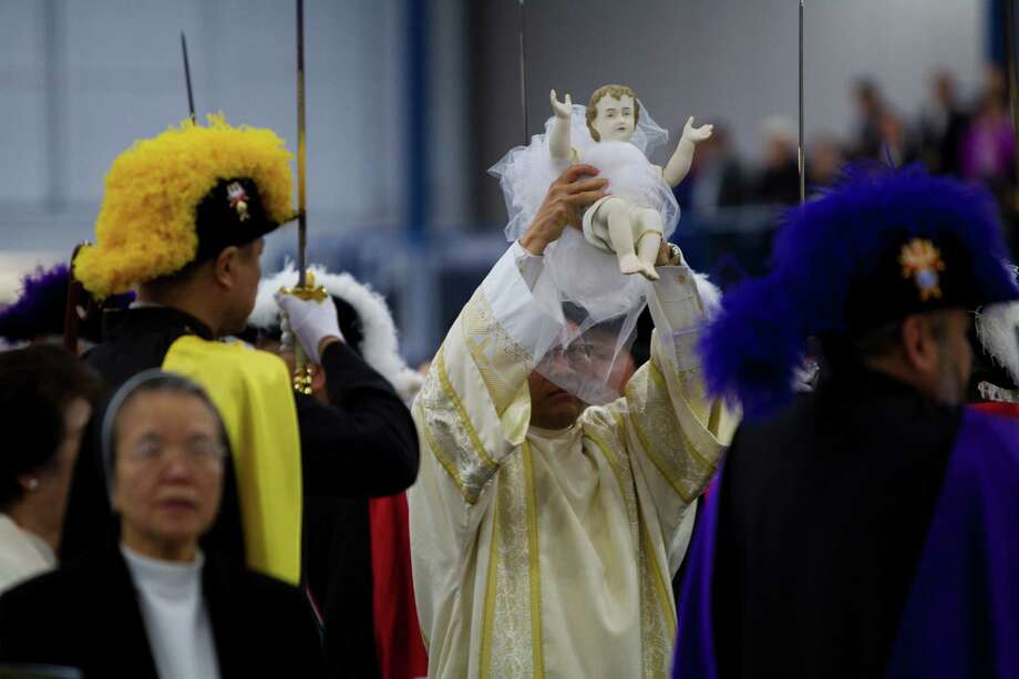 The procession carries baby Jesus to the Nativity. Photo: Marie D. De Jesus, Houston Chronicle / © 2013 Houston Chronicle