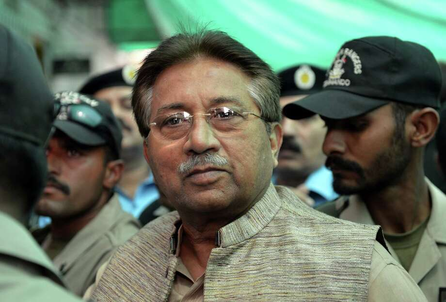 (FILES) In this photograph taken on April 20, 2013, Former Pakistani president Pervez Musharraf (C) is escorted by soldiers as he arrives at an anti-terrorism court in Islamabad. Pakistan's former military ruler Pervez Musharraf on  December 24, 2013, is scheduled to face trial for treason over his imposition of emergency rule in 2007, charges he has dismissed as politically motivated. The 70-year-old is expected to appear in person before a specially-convened court in the capital Islamabad, after legal efforts to have the tribunal ruled invalid failed. AFP PHOTO/AAMIR QURESHI/FILESAAMIR QURESHI/AFP/Getty Images Photo: AAMIR QURESHI, Staff / AFP ImageForum