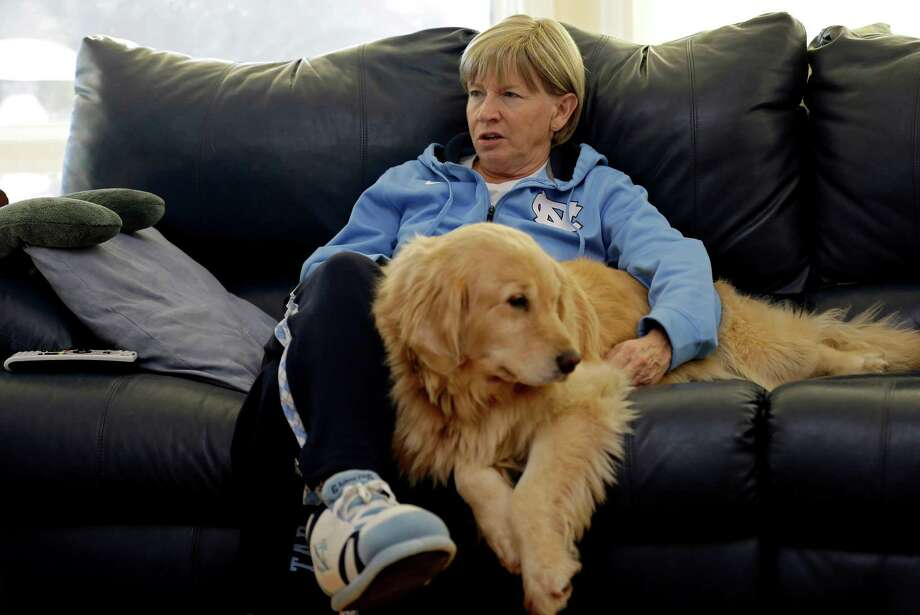 In this Wednesday, Dec. 18, 2013, photo, North Carolina women's basketball coach Sylvia Hatchell relaxes at home with her dog Maddie in Chapel Hill, N.C. After being diagnosed with leukemia, Hatchell has temporarily stepped away from her coaching duties to focus on her treatment. (AP Photo/Gerry Broome) ORG XMIT: NCGB202 Photo: Gerry Broome / AP