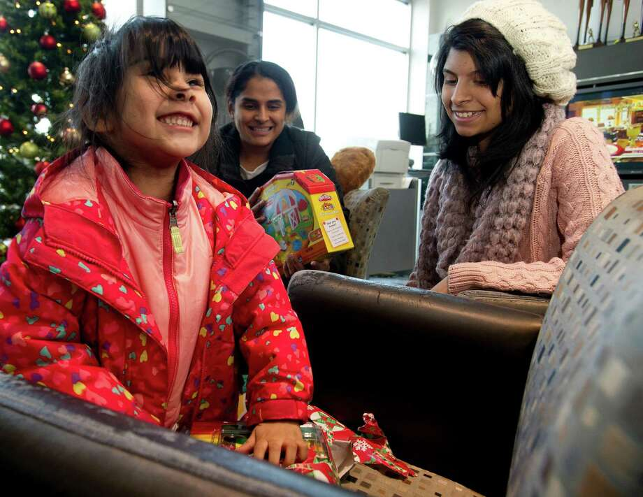 Sarahi Ordonez, 3, opens gifts at Toyota of Stamford on Thursday, December 19, 2013. The gifts, which were for Sarahi as well as her mother, Jacqueline Silva, and sister, Natalia Ordonez, 16, were given to the family to replace some of the things they lost in a major house fire. The money for the gifts was raised at the marathon relay at Stamford Toyota. Gifts included toys for Sarahi, a laptop for Natalia, and gift cards for furniture for the family. Photo: Lindsay Perry / Stamford Advocate