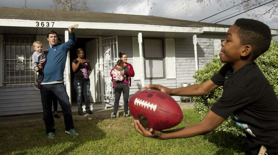 Brian Cushing (left) plays catch with Darius Montgomery outside the home of Darius' mother, Evelyn Smith. The Texans LB is finding life no longer defined by football after his latest injury. Photo: Brett Coomer / Houston Chronicle / © 2013 Houston Chronicle
