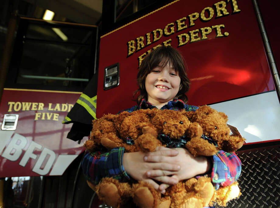 Vladimir Romano, 10, of Redding, holds an armful of the 24 teddy bears that he donated to the Bridgeport Fire department at fire department headquarters in Bridgeport, Conn. on Tuesday, December 24, 2013. Romano, who raises money to purchase the bears by running a summer lemonade stand, has donated 400 bears to area fire departments over the last three years. Photo: Brian A. Pounds / Connecticut Post