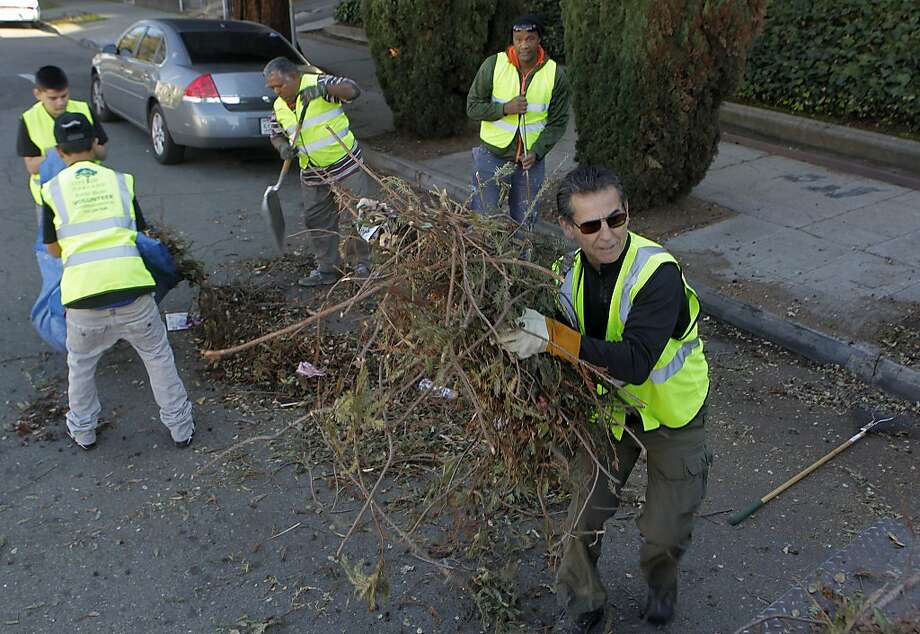City Councilman Noel Gallo (right) and a team of volunteers picks up trash dumped on Champion Street in Oakland. Photo: Paul Chinn, The Chronicle