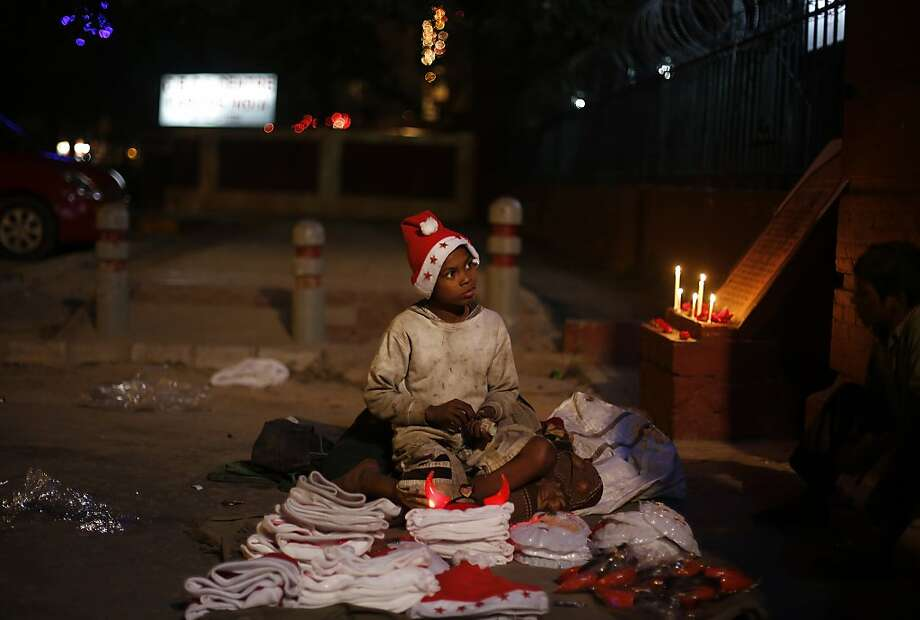 A young Indian boy sells Christmas merchandise outside the Sacred Heart's Cathedral in New Delhi, India, Tuesday, Dec. 24, 2013. Though Hindus and Muslims comprise the majority of the population in India, Christmas is celebrated with much fanfare. (AP Photo/Altaf Qadri) Photo: Altaf Qadri, Associated Press