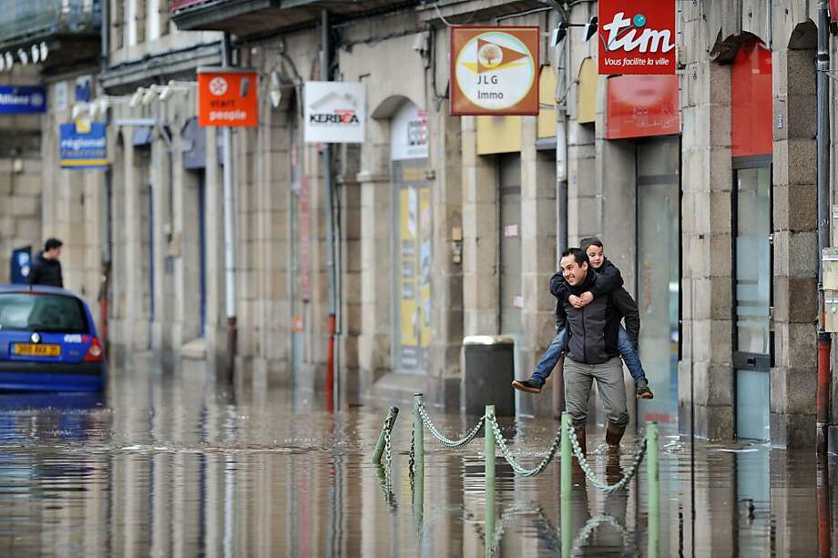 A man carries a boy in a flooded street in Morlaix, Britanny, where the city center is under 1.4 metres (four feet) of water on December 24, 2013. Gale-force winds and pounding rain lashed Britain and France, killing at least two people, disrupting Christmas travel and leaving tens of thousands without power.  A total of 240,000 French homes, mainly in the northwestern region of Brittany, were without electricity on Tuesday, according to power supplier ERDF.     AFP PHOTO / FRANK PERRYFRANK PERRY/AFP/Getty Images Photo: Frank Perry, AFP/Getty Images