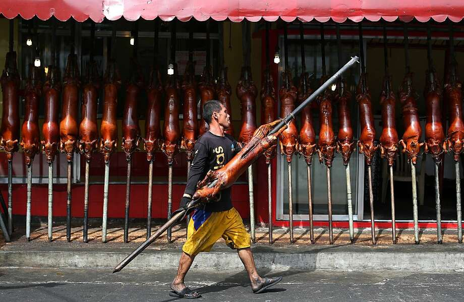 """A worker carries roasted pig outside a store in Quezon city, north of Manila, Philippines on Tuesday, Dec. 24, 2013. Roasted pig is traditionally served during a Christmas eve dinner called """"Noche Buena"""" in this predominantly Roman Catholic nation. Photo: Aaron Favila, Associated Press"""