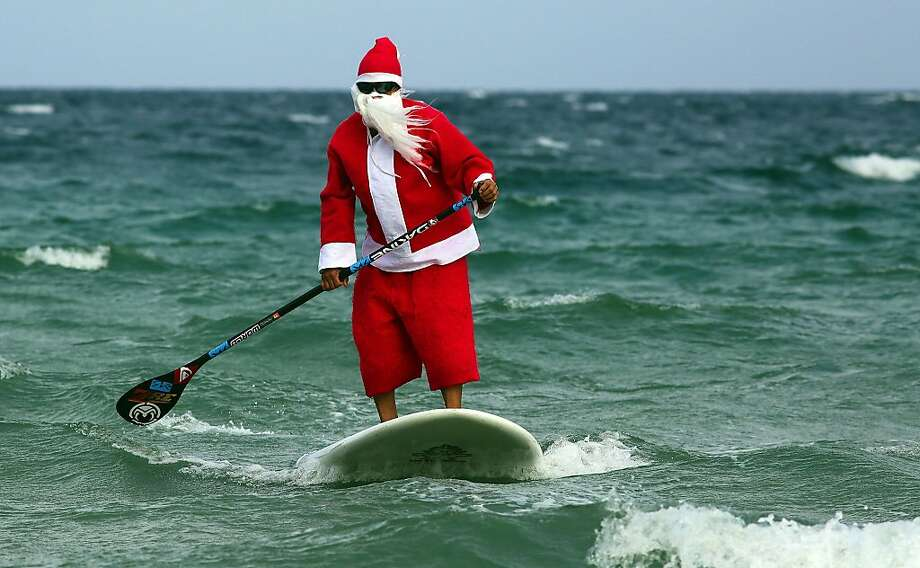 Santa Claus, aka Roray Kam, rides the waves off of Ft. Lauderdale, Fla., on Christmas Eve on Tuesday, Dec. 24, 2013. (Mike Stocker/Sun Sentinel/MCT) Photo: Mike Stocker, McClatchy-Tribune News Service