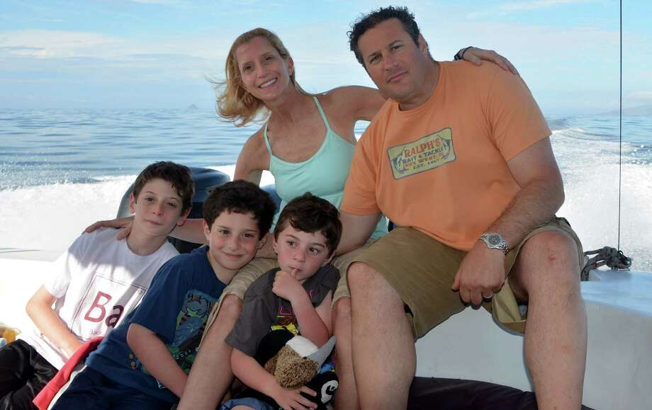 Blake Katzman, front left, with his Westport family in a boat off the Galapagos Islands, where they traveled earlier this year courtesy of the Make-A-Wish Foundation. With Blake are his parents Rachel and Dan Katzman, and brothers Matthew and Kyle. Photo: Contributed Photo / Westport News contributed