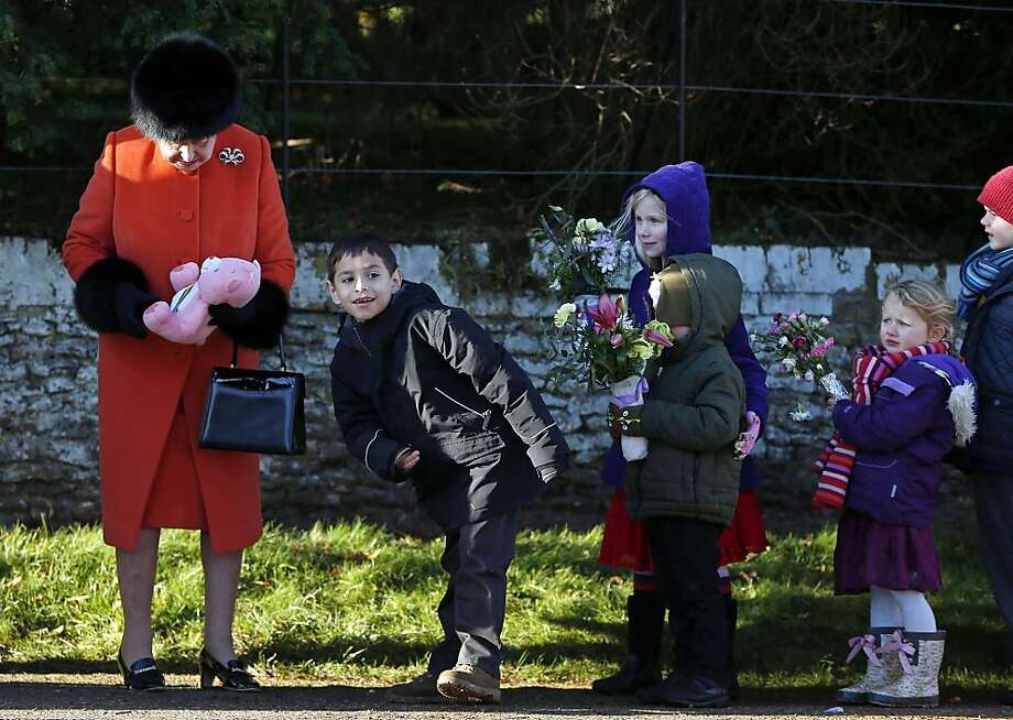 Children queue to give gifts and flowers to Britain's Queen Elizabeth II (L) following a traditional Christmas Day Church Service at Sandringham in eastern England, on December 25, 2013. Photo: Adrian Dennis, AFP/Getty Images