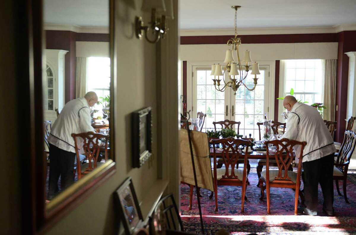 Bed and breakfast owner John Vouros clears a table after serving guests breakfast at the Dana-Holcombe House in Newtown, Conn. on Wednesday, Dec. 25, 2013. The inn keeps guests during the holidays and the owners enjoy their company, as it's part of their Christmas tradition.