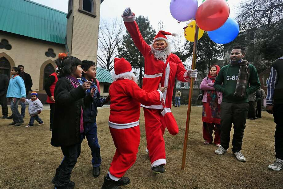 Indian Christians dressed as Santa Claus dance after offering Christmas prayers at the holy family Catholic Church in Srinagar, India, Wednesday, Dec. 25, 2013. Christmas is a national holiday in India, marked by millions of all religions and faiths. Photo: Dar Yasin, ASSOCIATED PRESS