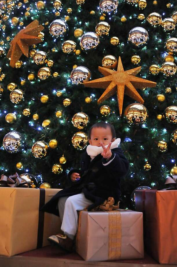 A little boy poses for photos with a Christmas tree in the Taipei Main Station on December 25, 2013. Photo: Afp