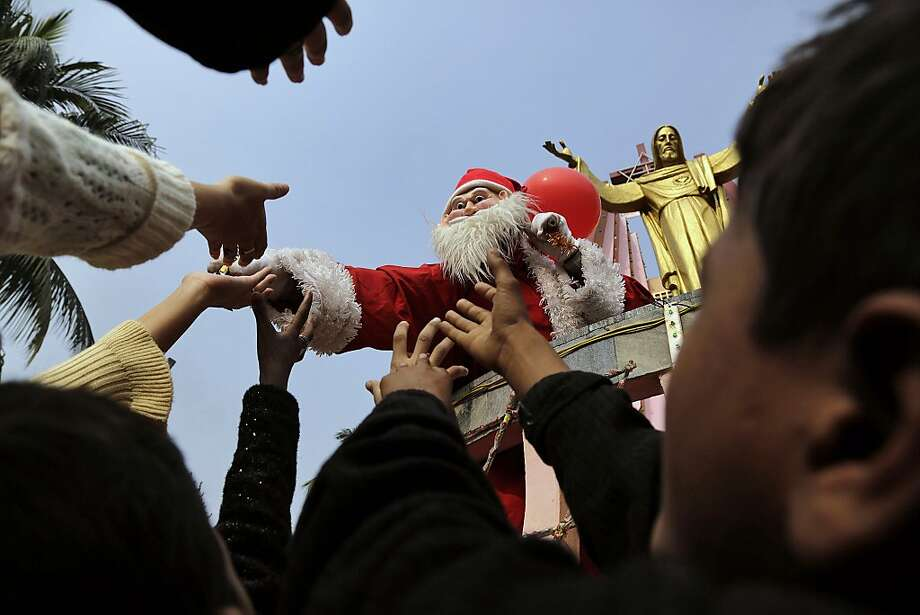A man dressed as Santa Claus distributes sweets to children on the occasion of Christmas outside a church in Gauhati, India, Wednesday, Dec. 25, 2013. Although Christians comprise only two percent of the population among a Hindu majority, the holiday is observed across the country as an occasion to celebrate. Photo: Anupam Nath, AP