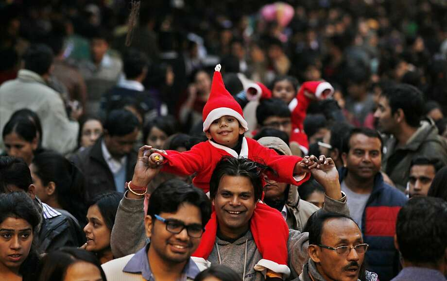 People enjoy Christmas in Janpath Market on December 25, 2013 in New Delhi, India. Despite Christians forming a little over two percent of the billion plus population in India, with Hindus comprising the majority, Christmas is celebrated with fanfare and zeal throughout the country. Photo: Hindustan Times, Hindustan Times Via Getty Images