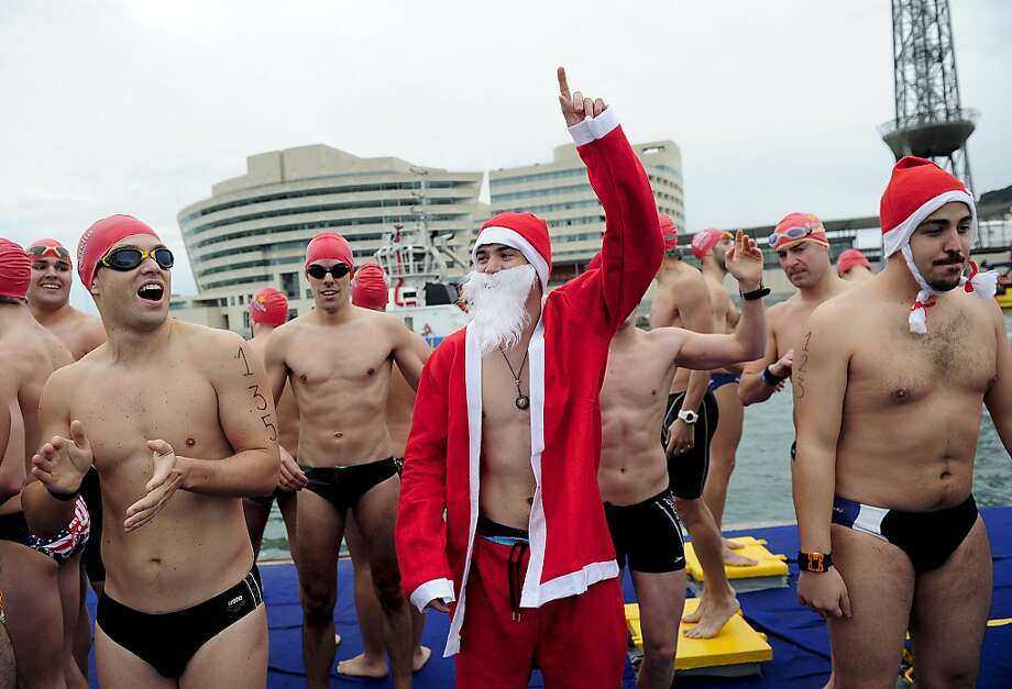 A participant in a Santa Clause costume gestures before the start of the104th edition of the Copa Nadal (Christmas Cup) in Barcelona's Port Vell on December 25, 2013. The traditional 200-meter Christmas swimming race gathered around 400 participants on Barcelona's old harbour. Photo: Josep Lago