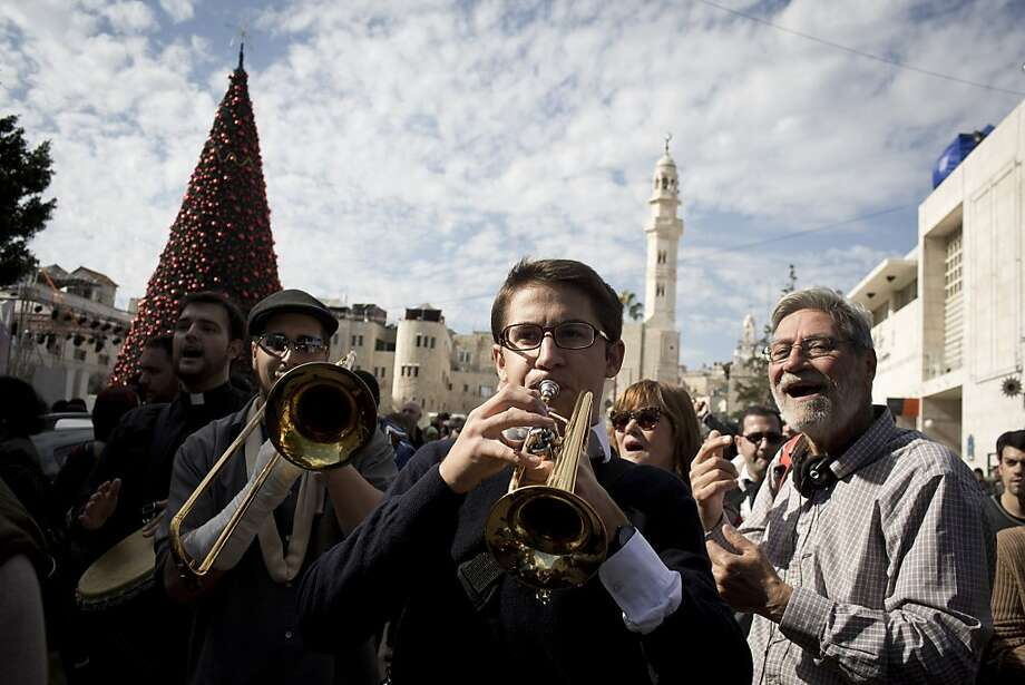 Christian worshippers play music as the enter the Church of the Nativity on December 25, 2013 in Bethlehem, West Bank. Every Christmas pilgrims travel to the church where a gold star embedded in the floor marks the spot where Jesus was believed to have been born. Photo: Oren Ziv, Getty Images